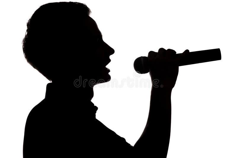 Schattenbild eines jungen begabten Mannes, der in ein microphon singt stockfotos