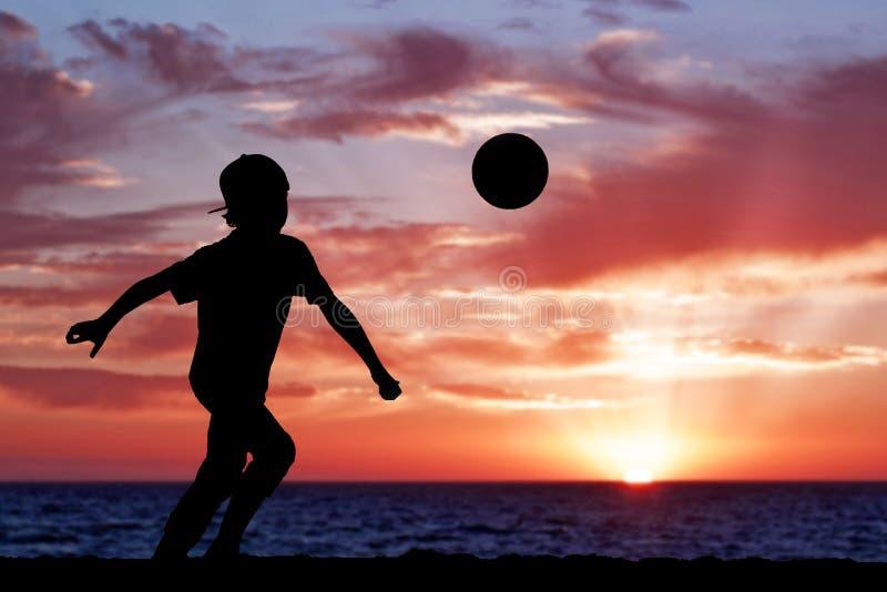 Schattenbild eines Jungen, der Fußball oder Fußball an spielt lizenzfreie stockfotografie