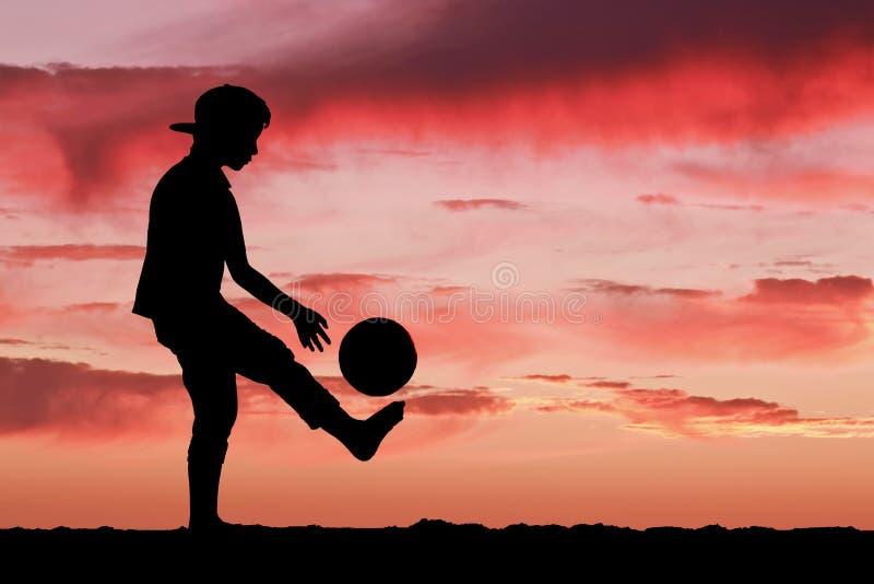 Schattenbild eines Jungen, der Fußball oder Fußball an spielt stockfotografie