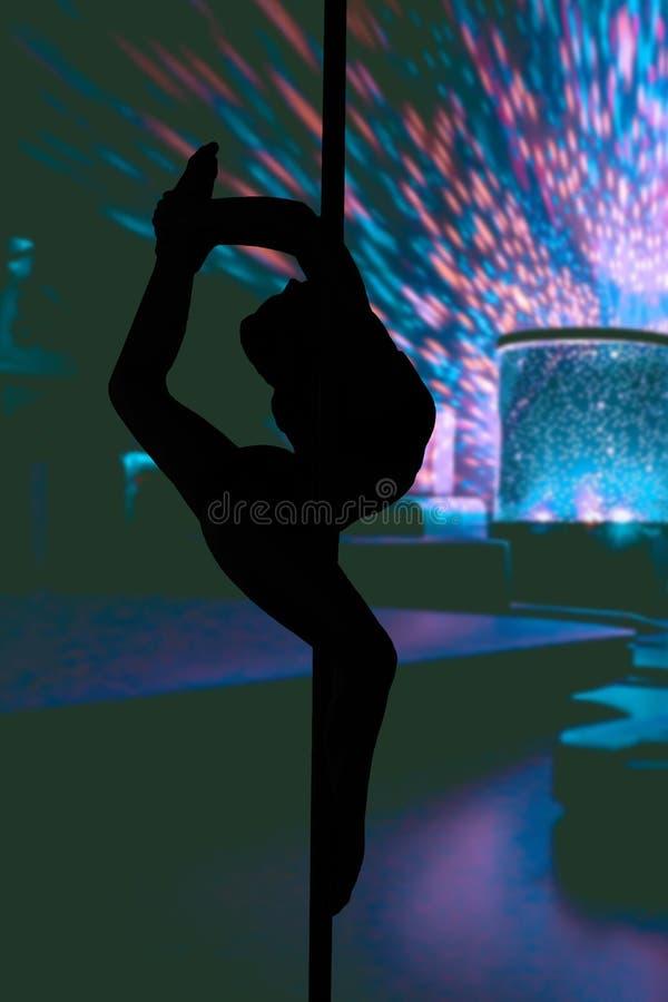 Schattenbild eines jungen flexiblen Mädchens, das in einem Tanzenpfosten durchführt in einem Striptease-Club hängt vektor abbildung