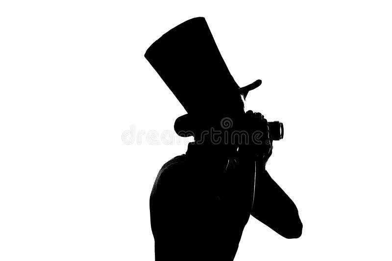 Schattenbild eines jungen Fotografen mit Kamera stockbilder