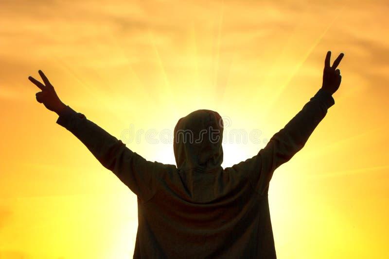 Schattenbild eines jungen Kerls auf dem Hintergrund des Sonnenuntergangs übergibt das Halten in den verschiedenen Richtungen stockbilder