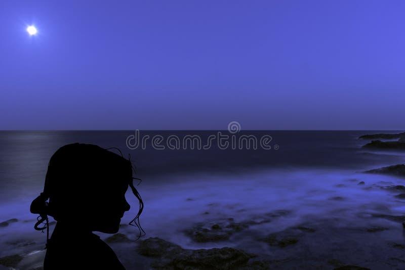 Schattenbild eines jungen Mädchens mit dem Mond über dem Ozean in Los Cocoteros stockbilder