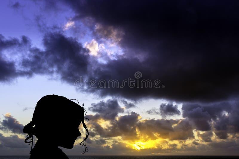Schattenbild eines jungen Mädchens mit Sonnenaufgang über dem Ozean im Hintergrund stockfotografie