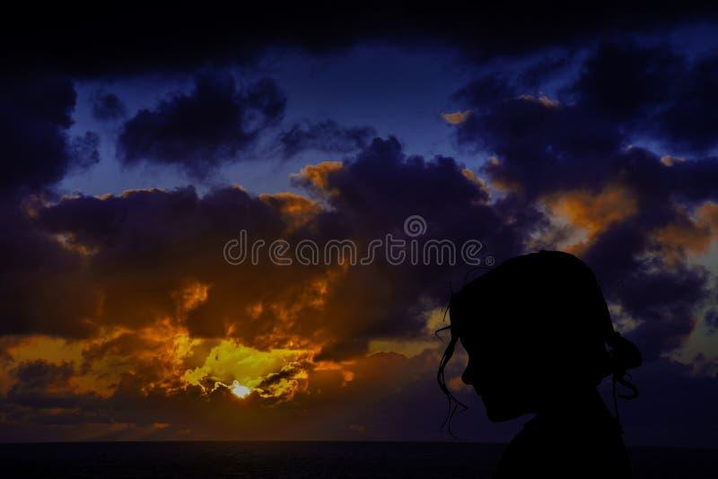 Schattenbild eines jungen Mädchens mit Sonnenaufgang über dem Ozean im Hintergrund stockbild
