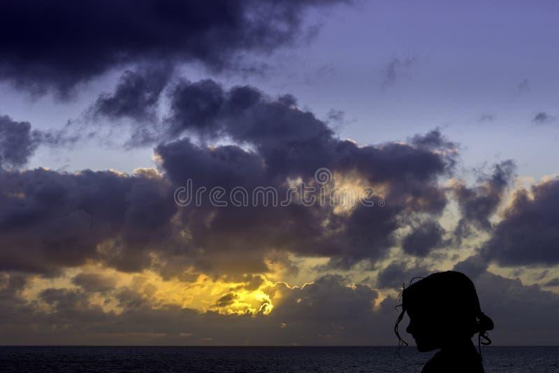Schattenbild eines jungen Mädchens mit Sonnenaufgang über dem Ozean im Hintergrund lizenzfreie stockfotos