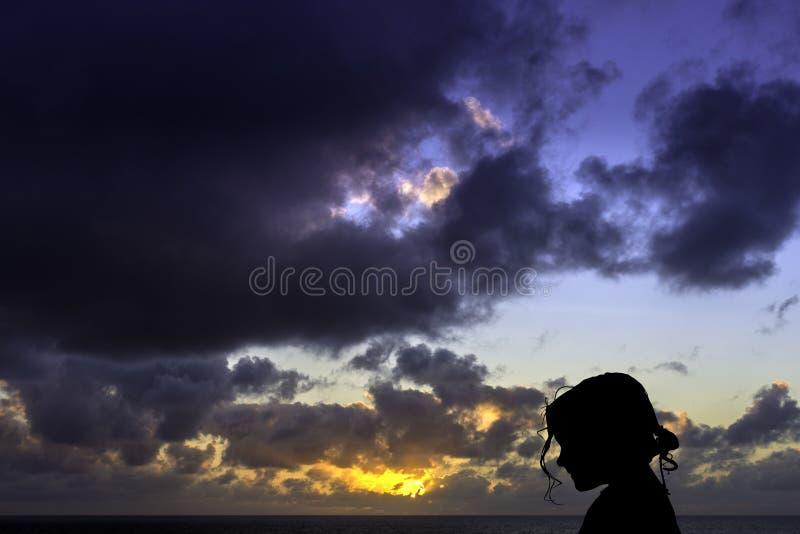 Schattenbild eines jungen Mädchens mit Sonnenaufgang über dem Ozean im Hintergrund stockfoto
