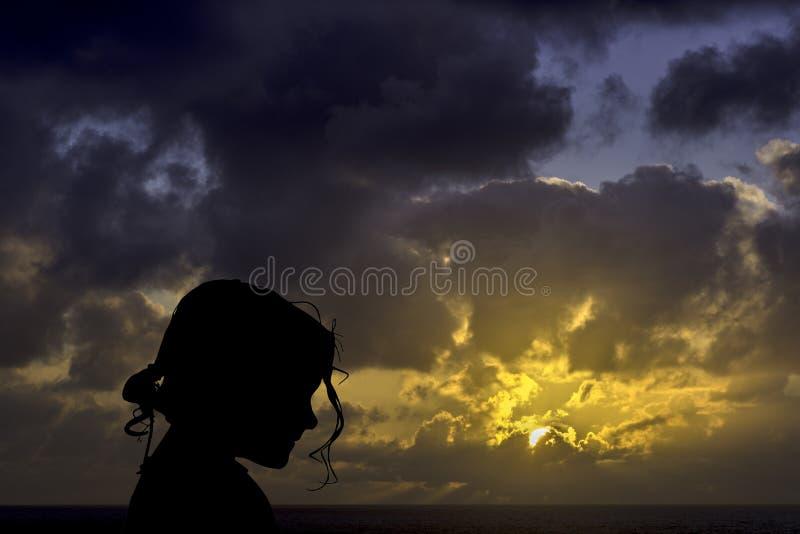 Schattenbild eines jungen Mädchens mit Sonnenaufgang über dem Ozean im Hintergrund lizenzfreie stockfotografie