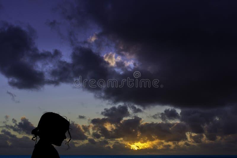 Schattenbild eines jungen Mädchens mit Sonnenaufgang über dem Ozean im Hintergrund stockbilder