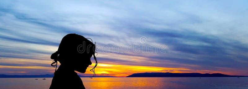 Schattenbild eines jungen Mädchens mit Sonnenuntergang über dem adriatischen Meer im Hintergrund - Makarska lizenzfreies stockfoto