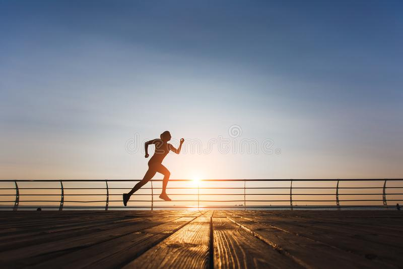 Schattenbild eines jungen schönen athletischen Mädchens mit dem langen blonden Haar in der schwarzen Kleidung, die bei Sonnenaufg stockfoto
