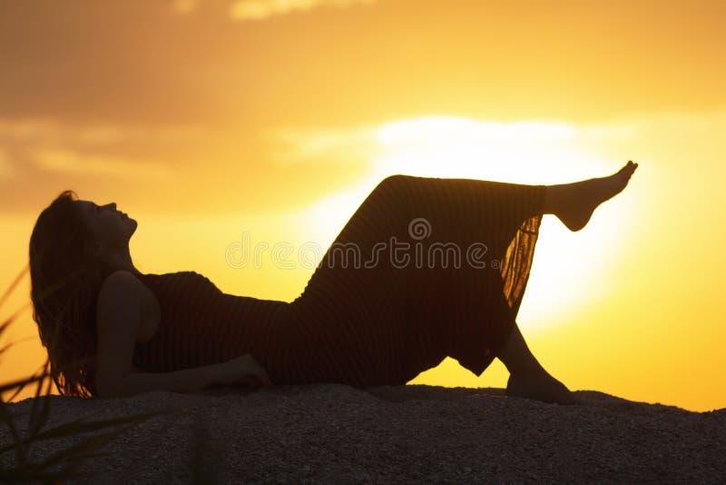 Schattenbild eines jungen schönen Mädchens, das in einem Kleid auf dem Sand liegt und den Sonnenuntergang, die Frauenfigur auf de lizenzfreie stockbilder