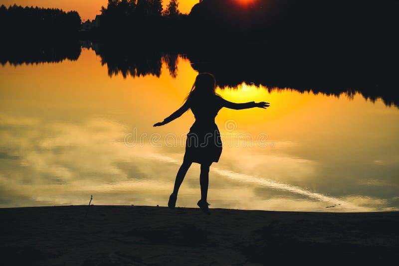 Schattenbild eines jungen schönen Mädchens in einem Sprung auf einem Hintergrund eines Sonnenuntergangs im Reflexionsteich lizenzfreies stockbild