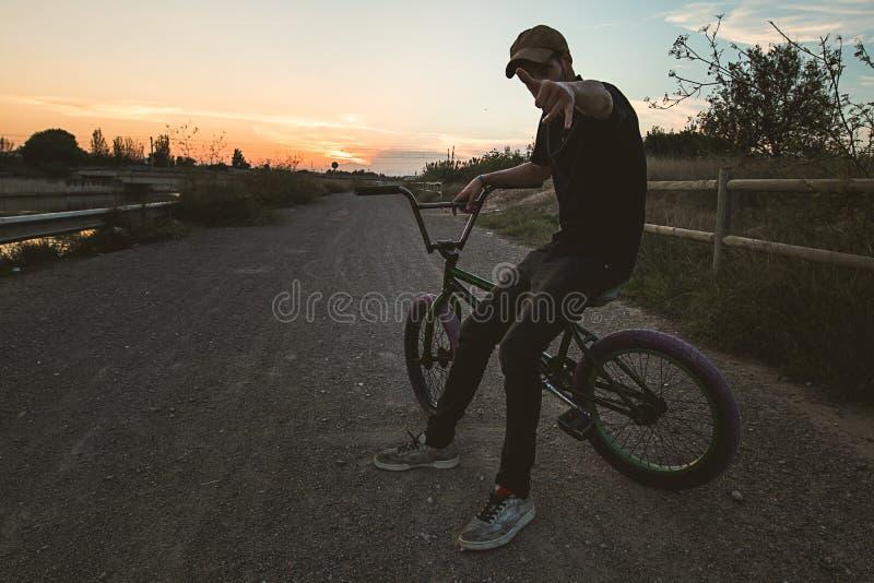 Schattenbild eines Kerls mit einem bmx Fahrrad lizenzfreie stockfotos