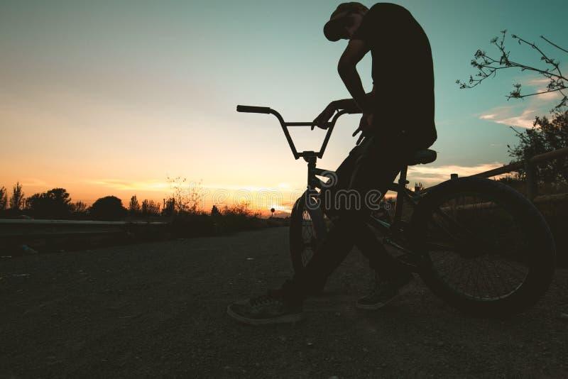 Schattenbild eines Kerls mit einem bmx Fahrrad lizenzfreie stockbilder