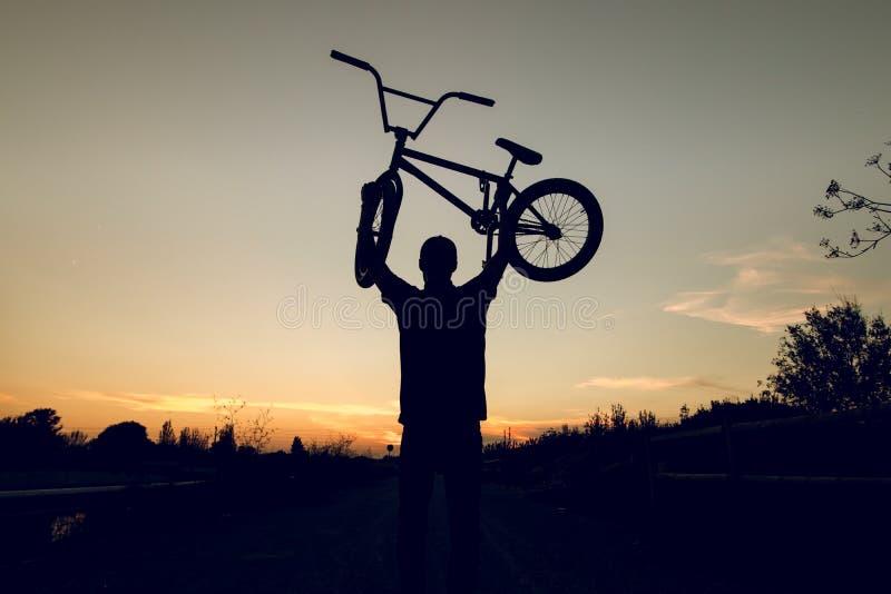Schattenbild eines Kerls mit einem bmx Fahrrad stockbild