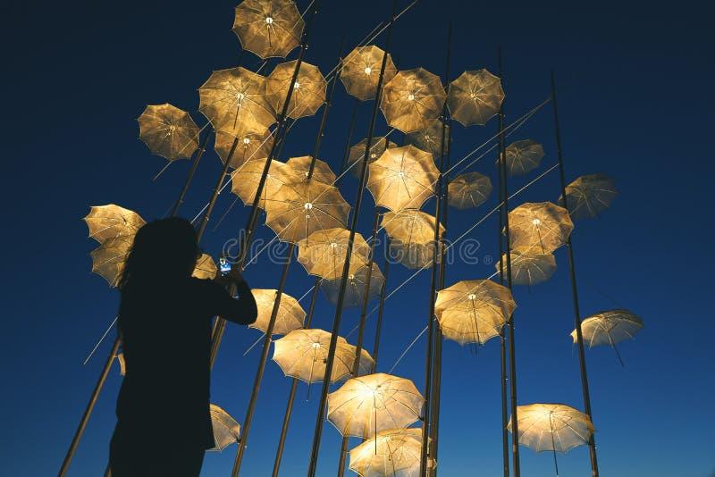 Schattenbild eines Mädchens, das die Regenschirme, Saloniki - Gree schießt stockfoto