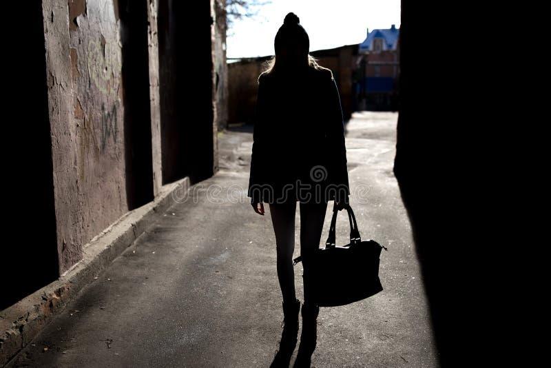 Schattenbild eines Mädchens mit einer Tasche stockbilder
