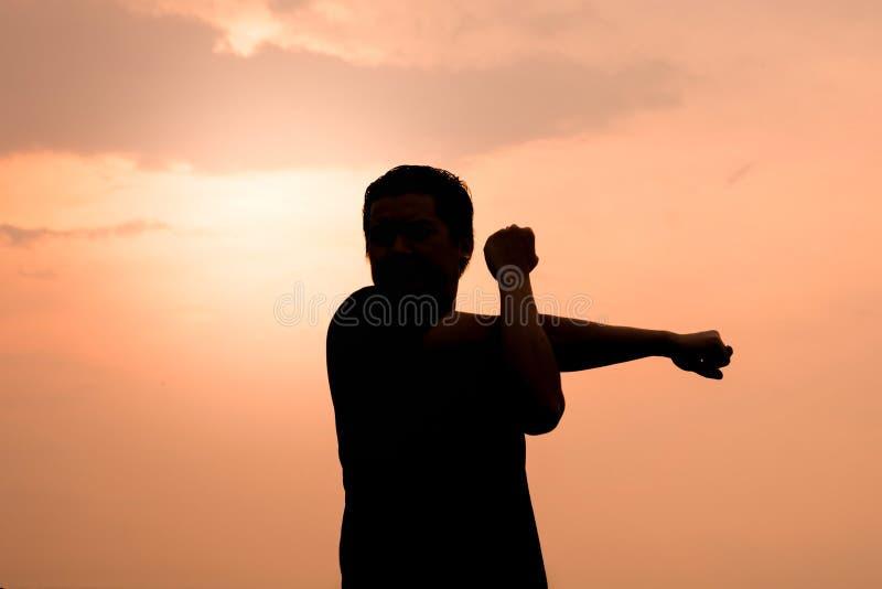 Schattenbild eines Mannes dehnen die Muskelübungen aus lizenzfreies stockfoto