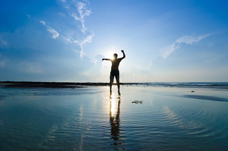 Schattenbild eines Mannes, der über Sonne springt lizenzfreie stockfotos