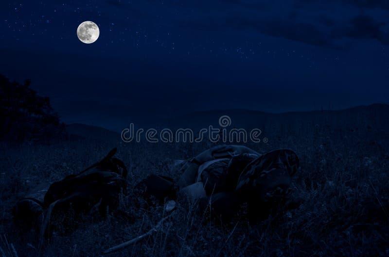 Schattenbild eines Mannes, der auf einem Gras an der Spitze des Berges liegt und oben gegen hellen Vollmond und Sterne auf nächtl stockfotos