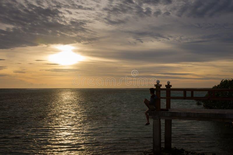 Schattenbild eines Mannes, der das Meer allein am Rand der Brücke mit schönem Sonnenunterganghimmel sitzt und betrachtet Königlic lizenzfreies stockfoto