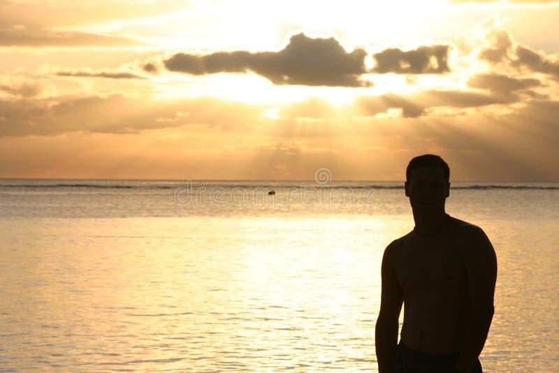 Schattenbild eines Mannes, der den Sonnenuntergang überwacht lizenzfreie stockbilder