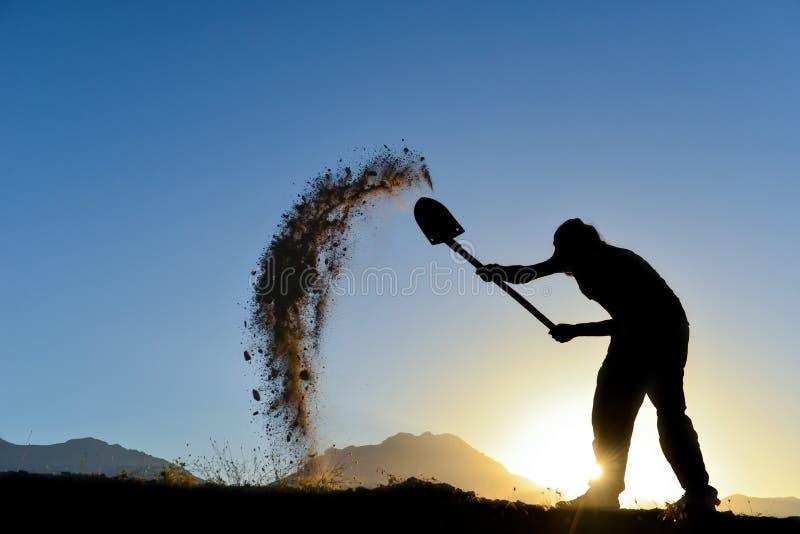 Schattenbild eines Mannes der der Boden mit einer Schaufel stockfotografie