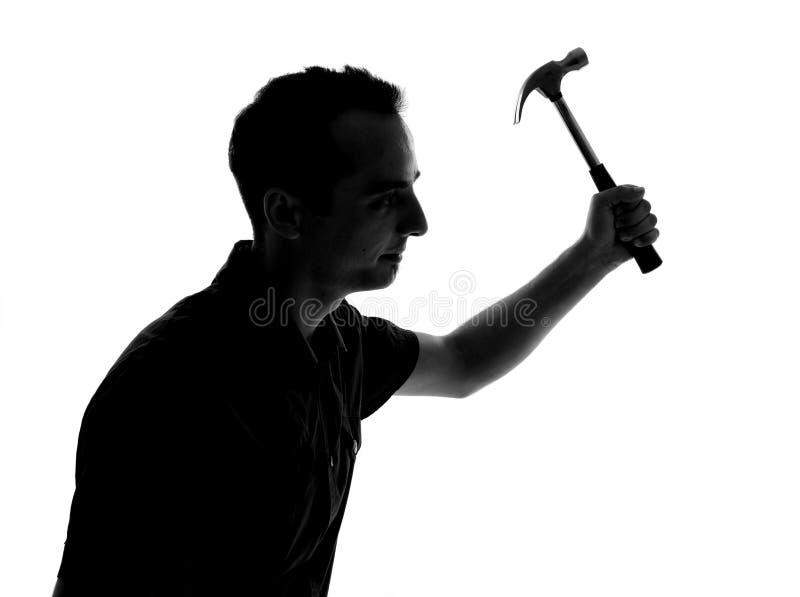Schattenbild eines Mannes, der mit Hammer arbeitet lizenzfreie stockbilder