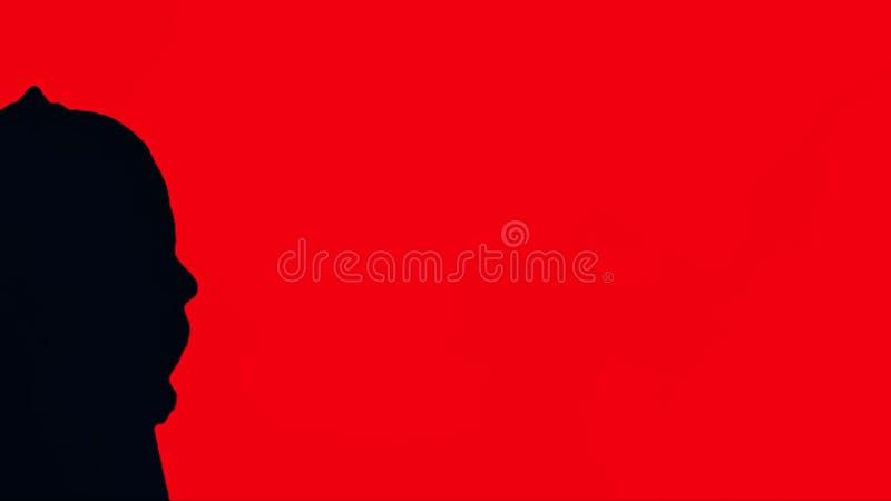 Schattenbild eines Mannes in der schwarzen Haube, roter Hintergrund Porträt des unsichtbaren Mannes in der Haube mit rotem Vorhan lizenzfreies stockbild