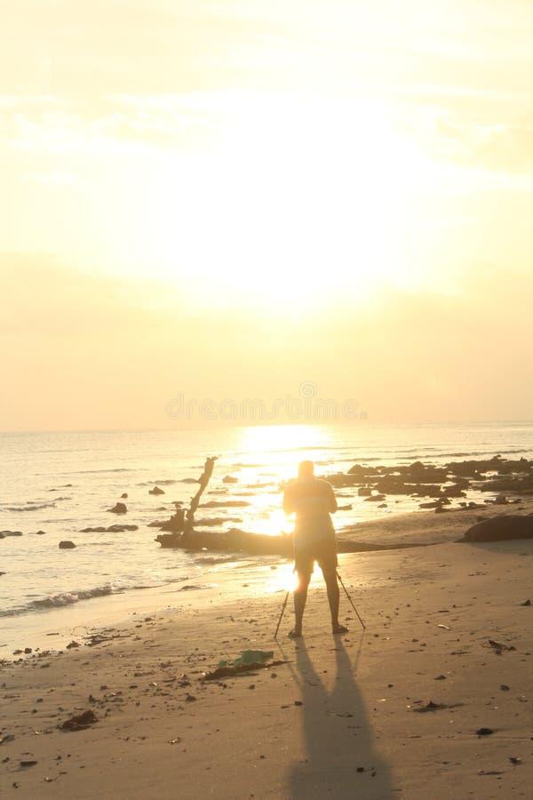 Schattenbild eines Mannes, der Sonnenaufgang an einem Strand gefangennimmt stockfotos