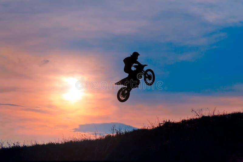 Schattenbild eines Motorradreiters, der auf Sonnenuntergang bremst lizenzfreie stockbilder