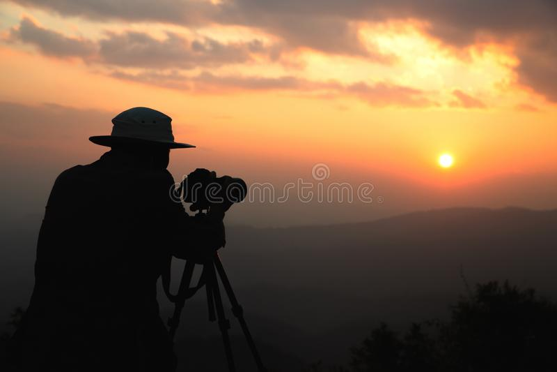 Schattenbild eines Naturphotographen, der einen Sonnenuntergang und einen sch?nen orange Himmel schie?t, Fotos bei Sonnenuntergan lizenzfreie stockfotos