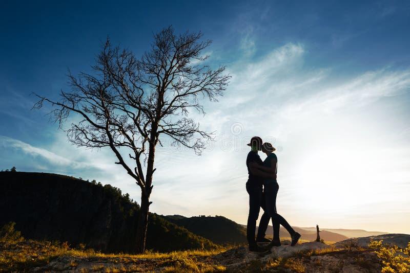 Schattenbild eines Paares in der Liebe Kerl und Mädchen, die bei Sonnenuntergang umarmen Verbinden Sie Reisen Liebhaber in der Na stockbild