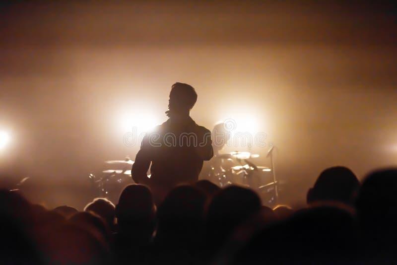 Schattenbild eines Sängers und des Schlagzeugers auf dem Stadium eines musikalischen Rockfestivals lizenzfreies stockbild