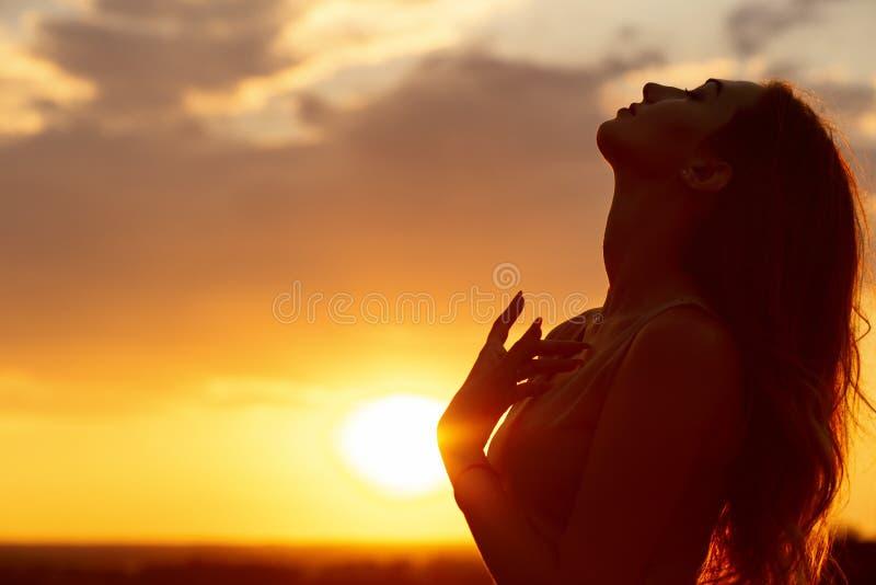 Schattenbild eines schönen Mädchens bei Sonnenuntergang auf einem Gebiet, Gesichtsprofil der jungen Frau lizenzfreie stockbilder