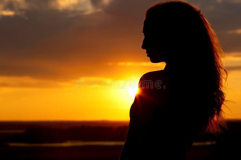 Schattenbild eines schönen Mädchens bei Sonnenuntergang, Gesichtsprofil der jungen Frau Natur genießend stockbild
