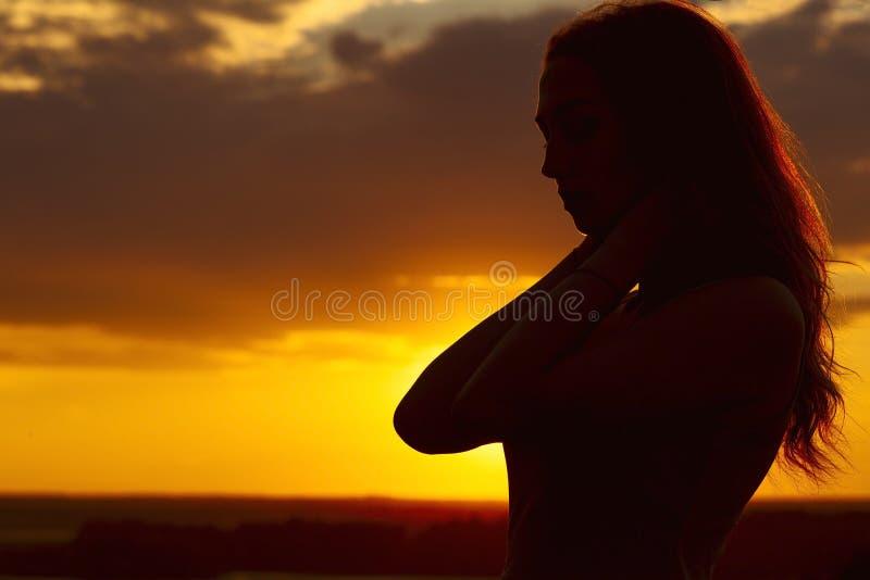 Schattenbild eines schönen romantischen Mädchens bei Sonnenuntergang, Gesichtsprofil der jungen Frau mit dem langen Haar bei heiß stockfotografie