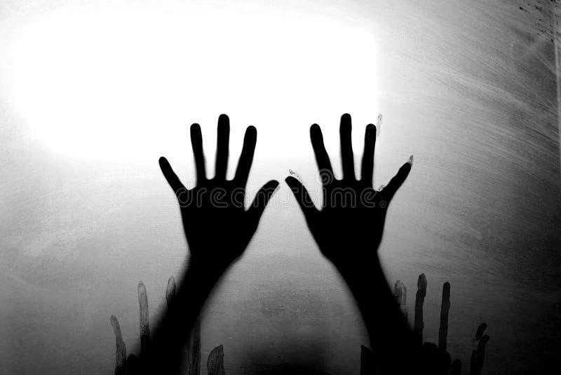 Schattenbild erschrockene Mädchenhand hinter Glastür Grausigkeitshintergrundkonzept stockfotografie