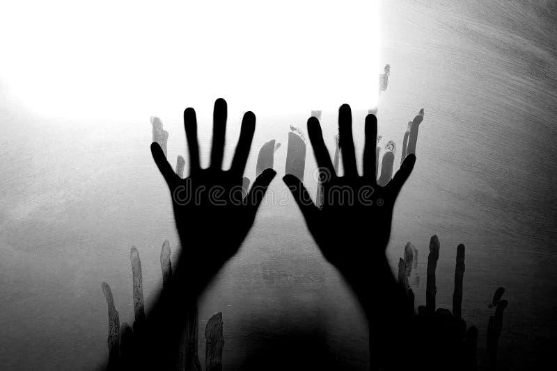 Schattenbild erschrockene M?dchenhand hinter Glast?r Grausigkeitshintergrundkonzept lizenzfreie stockfotografie