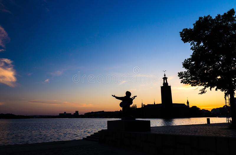 Schattenbild Evert Taube von Statue und Stockholmvon Rathaus, Schweden lizenzfreie stockfotos