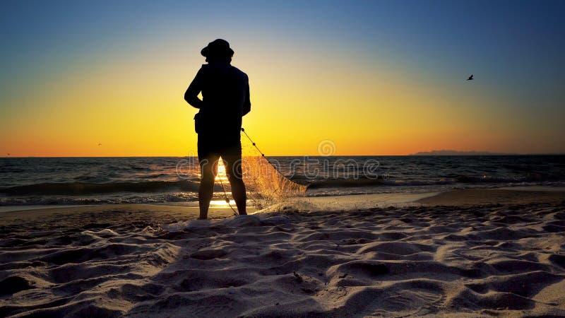 Schattenbild-Fischer, die Fischernetze verwenden stockfotos