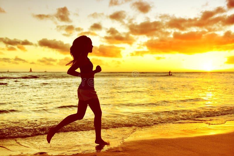 Schattenbild-Frau, die am Strand während des Sonnenaufgangs rüttelt stockbilder