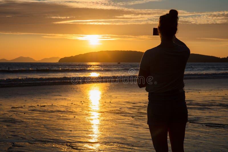 Schattenbild-Frauen-fotografierender Sonnenuntergang am Strand stockfotos