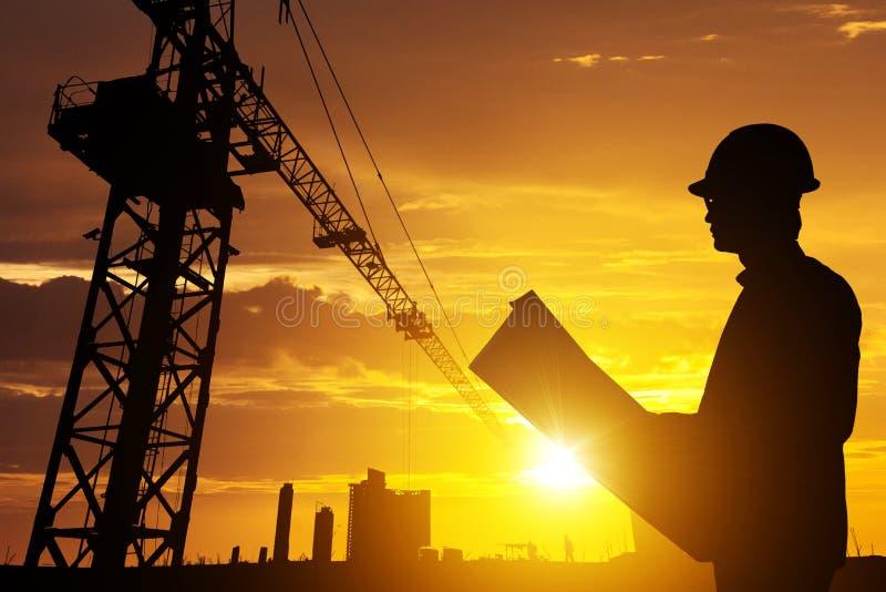 Schattenbild-Geschäftsmanningenieur, der Plan in einer Baustelle über unscharfem Baustelle-Filmkornfortschritt schauen und starke lizenzfreie stockfotografie