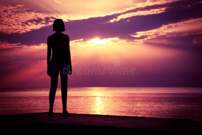 Schattenbild junge Frauen-des aufpassenden Seesonnenuntergangs stockbild