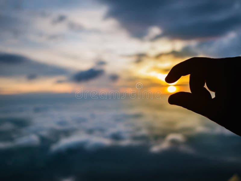 Schattenbild-menschliche Hand, welche oben die Auswahl die Sonne auf schönem Sonnenaufgang mit idyllischem Wolke Himmel am Morgen stockfotografie