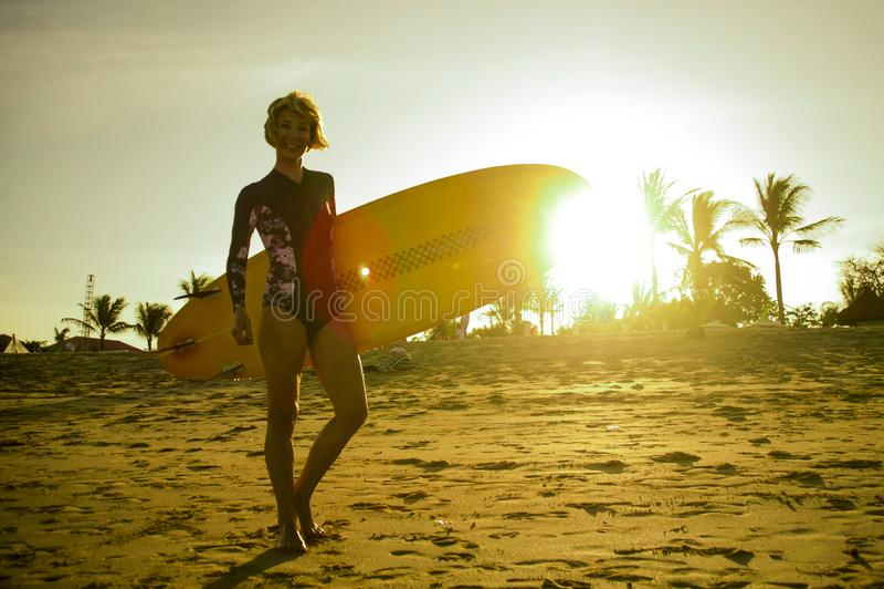 Schattenbild mit Sonnenblendenfleck des jungen tragenden Brandungsbrettes des glücklichen und attraktiven Surfermädchens, das auf lizenzfreies stockfoto