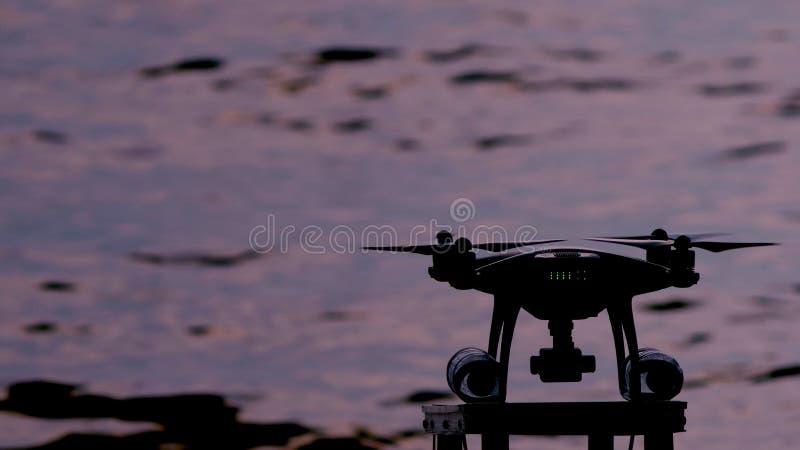 Schattenbild, Nahaufnahme Berufs-quadcopter fliegt gegen das Meer lizenzfreie stockfotos