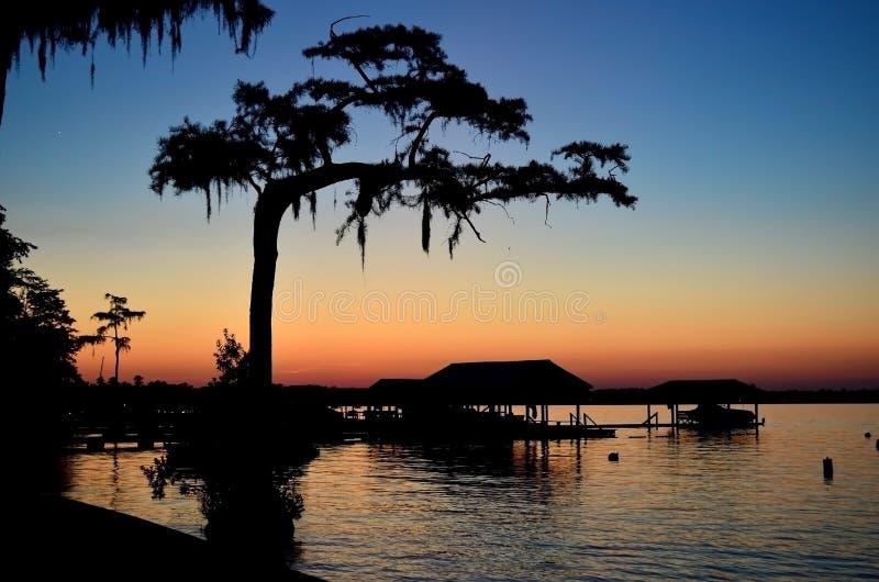 Schattenbild von Bootshäusern und von Bäumen bei Sonnenuntergang stockbild